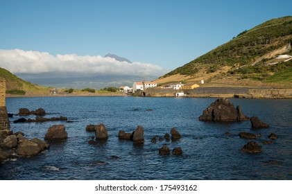 Bay in the Azores with Pico mountain covered with clouds in the background
