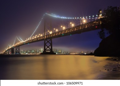 The Bay Bridge of San Francisco, California is shrouded in fog as the lights of the city and the bridge collect in the water below.