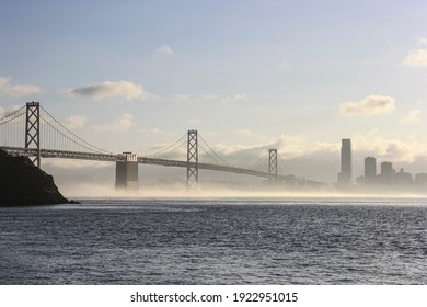 Bay Bridge span into the city San Francisco with fog rolling underneath