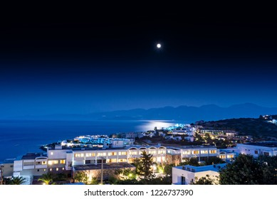 The bay at Elounda in Crete in moonlight. Buildings are lit up and the light from the moon is reflected in the sea.  Hills can bee seen in the far distance.