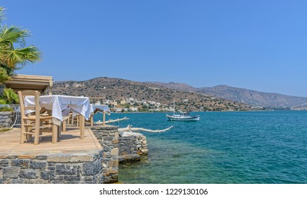 The bay at Elounda in Crete.  Tables are set for diners and a boat is moored nearby.  A range of hills are in the distance.