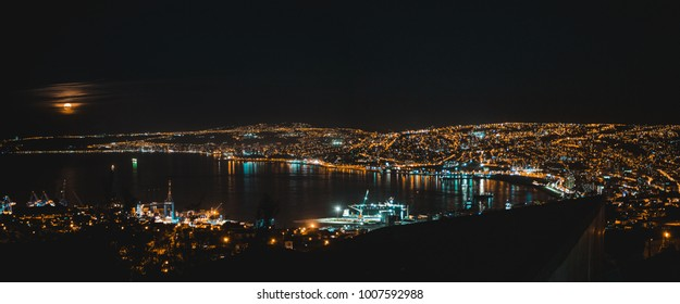 The bay of the industrial port town of Valparaíso, Chile, lit up by city lights and a full moon