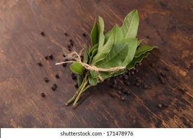 Bay leaves with black pepper corn in wooden background