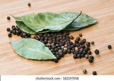 Bay leaves with black pepper corn on wooden deck