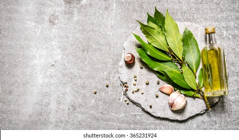 Bay leaves with garlic, pepper and olive oil on a stone stand. On the stone table.  Top view