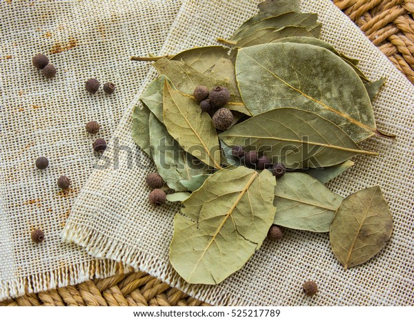 bay leaves on a straw background with pepper