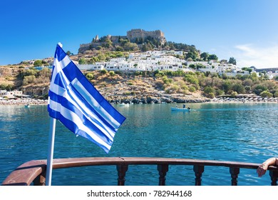 Bay of Lindos, Grrek flag and acropolis of Lindos in background (Rhodes, Greece)
