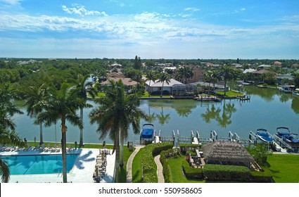 The bay in Naples, Florida with palm trees, grass, boat, swimming pool and views of the city, blue sky with clouds on a sunny day