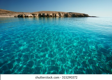 Bay in Rinia or Dilos with clear transparent swimming waters, Mykonos, Cyclades islands, Greece.