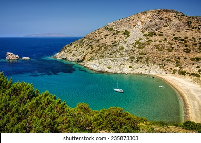 Bay in Syros island, Cyclades, Greece, with clear transparent waters and an anchored sailing boat.