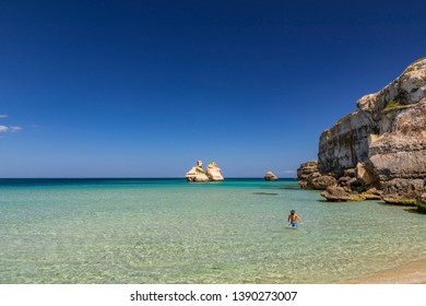 The bay of Torre dell'Orso, with its high cliffs, in Salento, Puglia, Italy. Turquoise sea and blue sky, sunny day. A child takes a bath and plays in the water. The stacks called the Two Sisters.