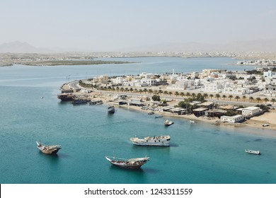 Bay with traditional wooden Dhow ships. Coastline of old city Sur in Sultanate of Oman.