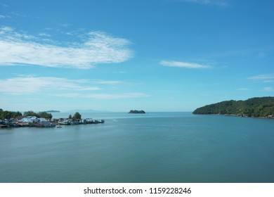 Bay viewpoint with end of the beach on right side and fishery village on left, sky sea and island scenic,open sea with very bright sky, ombre sky and sea scenery, fishing boat and ship in open sea.