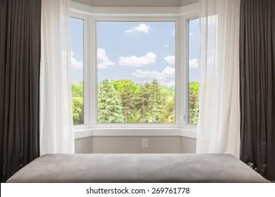 Fensterbucht mit Vorhängen, Vorhängen und Blick auf die Bäume unter dem Sommerhimmel