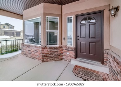 Bay window and glass paned wood front door at the facade of home with brick wall