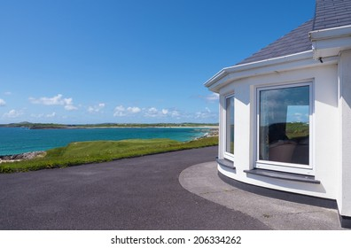 Bay window of a white beach house in Connemara, Ireland, with the Atlantic Ocean in the background.