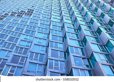 Bay windows in a modern building facade with window sections of aluminum, being tilted, in an residential high rise in New York City