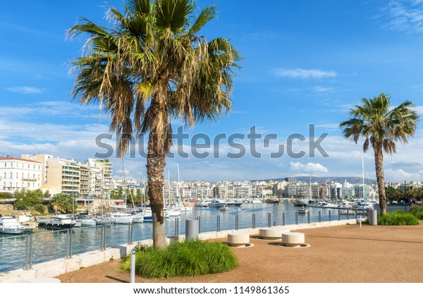 Bay of Zea or Pasalimani in Piraeus, Athens, Greece. Scenic view of a beautiful harbor with palm trees and sail boats. Panorama of the city with sea port. Luxury marine relax on the coast of Athens.