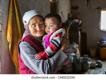bayan Ulgii, Mongolia, 30th September 2015: mongolian kazakh nomad granmother holding a boy on her lap inside a winter house