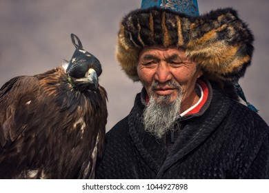 Bayan-Olgii, Mongolia - October 01, 2017: Golden Eagle Festifal. Portrait Of Picturesque Old Greybearded Mongolian Hunter Berkutchi In Traditional Clothes  With Golden Eagle Close Up. Hunter And Eagle