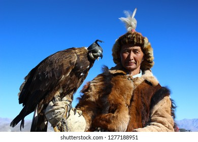 "BAYAN-OLGII PROVINCE, MONGOLIA - OCTOBER 07, 2018: Mongolians horsemen in traditional clothing with golden eagles posing during the festival of name ""The Golden Eagle Festival"""