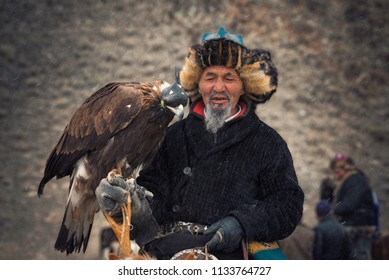 Bayan-Olgii, Western Mongolia - October 01, 2017: Golden Eagle Festifal. Portrait Of Picturesque Old Greybearded Mongolian Hunter ( Berkutci ) In Traditional Clothes  With Berkut On Hand.