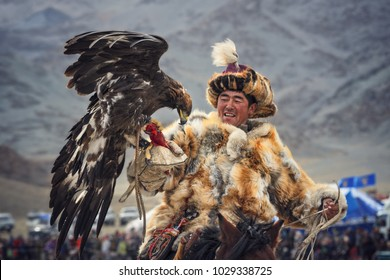 Bayan-Ulgii, Mongolia - October 01, 2017: Golden Eagle Festival. Impressive Mongolian Hunter In Traditional Clothes Of Fox Fur With A Golden Eagle On Hand.Falconry In Western Mongolia. Hunter And Bird