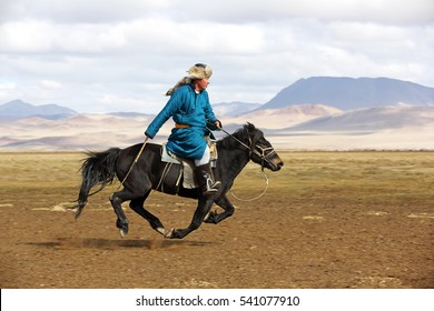 BAYAN-ULGII, MONGOLIA - SEP 25: Young man riding a horse running and action at his village of Western Mongolia on September 25, 2016. Most of the people in Mongolia still wearing traditional clothing