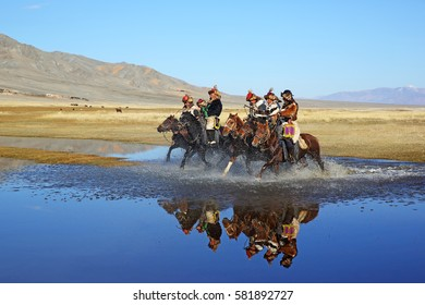 BAYAN-ULGII, MONGOLIA - SEP 26: Senior mongolian horsemen in traditional kazakh clothing running through the steppe reflecting in the water on morning of village sagsai his on September 26, 2016