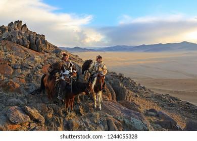 BAYAN-ULGII, MONGOLIA - SEP 27: Kazakh Eagle Hunter traditional ride a horse holding a golden eagle on his arm in desert mountain of Western Mongolia on September 27, 2016 in Bayan-Ulgii, Mongolia
