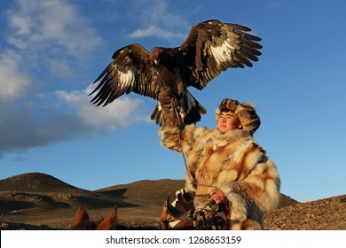 BAYAN-ULGII, MONGOLIA - September 28, 2016: Kazakh Eagle Hunter young traditional ride a horse holding a golden eagle on desert mountain in morning light of Western Mongolia in Bayan-Ulgii, Mongolia