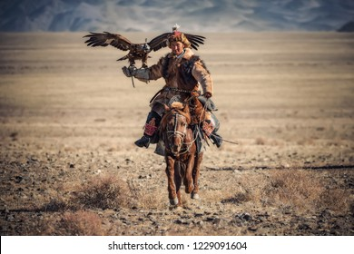 Bayan-Ulgii, Western Mongolia - October 07, 2018: Nomad Games, Golden Eagle Festival.  Sunny Day And Mongolian Nomad-Hunter With Great Golden Eagle On Hand Riding A Brown Horse Right On You