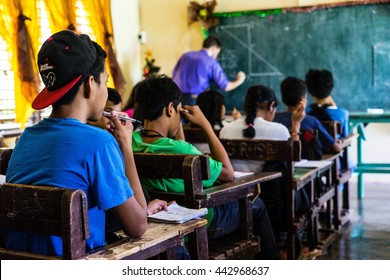 BAYBAY CITY, THE PHILIPPINES - December 2, 2015: A student follows along as his teacher, a volunteer with the United States Peace Corps, teaches in Baybay City, the Philippines on December 2, 2015.