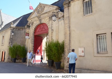 BAYEUX, FRANCE - AUG 12:  Visitors walk through the entry to the museum that houses the Bayeux Tapistry in Bayeux, France on August 12, 2016.