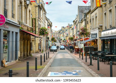 Bayeux, France - September 18 2018: Flags cross over the long, one way Rue Saint-Jean, the main street full of cafes and shops as the Normandy city of Bayeux, France blurs slightly in the distance