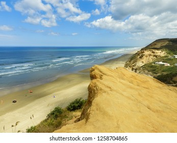 Baylys Beach and the Tasman Sea in New Zealand seen from a cliff on a sunny day
