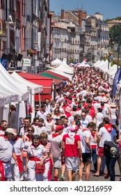 BAYONNE, FRANCE - AUGUST 2: Crowd of people dressed in white and red at the Summer festival (Fetes de Bayonne), on August 2, 2015 in Bayonne