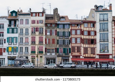 BAYONNE, FRANCE - CIRCA MARCH 2017: Unidentified people walk along the waterfront of the Nive River