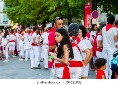 """BAYONNE, FRANCE - JULY31: Unknown people dressed in traditional red and white clothes at """"Fetes de Bayonne"""" festivals in the Northern Basque Country in the town of Bayonne, France on July 31st, 2017"""