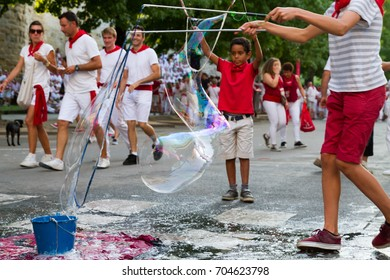 """BAYONNE, FRANCE - JULY31: Unknown people dresses in traditional red and white clothes at """"Fetes de Bayonne"""" festivals in the Northern Basque Country in the town of Bayonne, France on July 31st, 2017"""