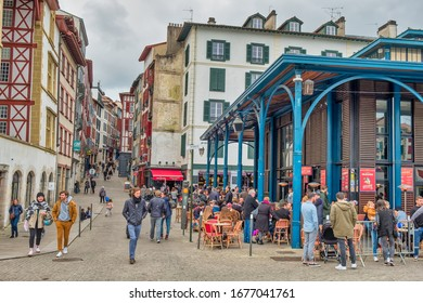 Bayonne, France - March 14, 2020; People having an aperitif on the terraces of the Bayonne market.
