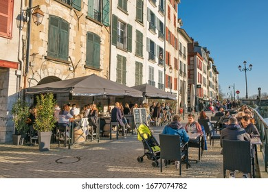 Bayonne, France - March 14, 2020; People having a drink on the terraces of the old town of Bayonne on a saturday at sunset.