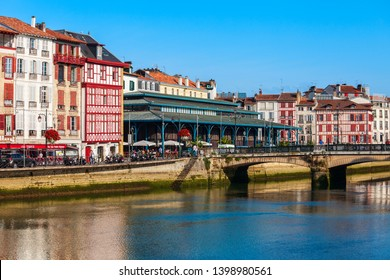 BAYONNE, FRANCE - SEPTEMBER 19, 2018: Main public market and colorful houses at the Nive river embankment in Bayonne town in France