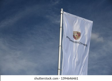 Bayreuth, Bavaria / Germany - May 20, 2018: Flag with Porsche logo against blue sky in Bayreuth, Germany - Porsche is a German automobile manufacturer specialized in high-performance sports cars