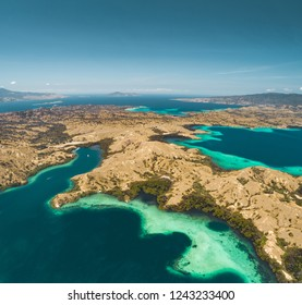 Bays, savanna lands, ocean. Komodo. Aerial shot. Spectacular panoramic view from above the stunning bays and savanna territory of Komodo National Park. Indonesia. Heritage Site. Overview drone shot.
