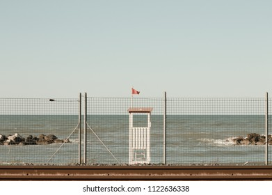 Baywatch tower with red flag behind the railway (Pesaro, Italy)