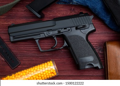 BB Gun, Old Airsoft Pistol Toy and Magazine with BB Gun Bullets on Wood Background.