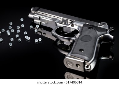 BB gun,gas airsoft pistol with bb bullets  on glass black, selective focus