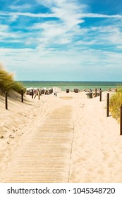 Bbeach sand, blue sky with clouds, beach chairs. People are sunbathing. The beach of the Baltic Sea, Germany resort.