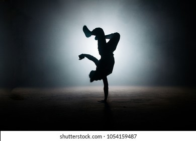 b-boy performing kick on yhe dark street. stylish position. dance form